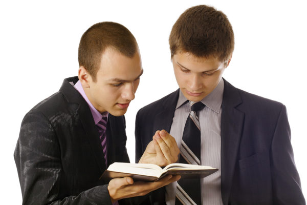 Young man explaining the bible to a teen boy during drug treatment